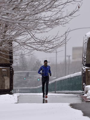 A runner jogs across  Weissman Memorial Bridge Wednesday. As of late afternoon, 5.6 inches of snow had been recorded in Great Falls, a new daily record for Nov. 1.