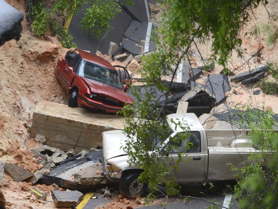 Two vehicles dropped about 40 feet into the bluffs when Scenic Highway collapsed at the 3800 block of the street in Pensacola on Wednesday, April 30, 2014. (AP Photo/Pensacola News Journal, Katie King)
