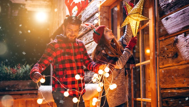 Couple on vacation at mountain cabin. Decorating porch with string lights for Christmas. Wearing knitted sweaters, hats and scarfs. Austrian Alps. Evening or night with beautiful yellow lights lightning the scenes.