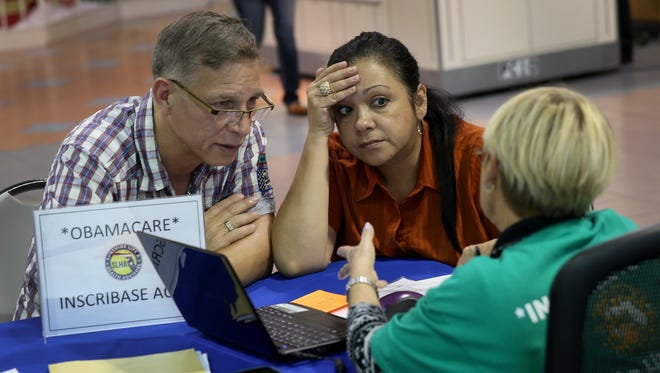 Angel Rivera, left, and his wife Wilma Rivera sit with Amada Cantera, an insurance agent with Sunshine Life and Health Advisors as they try to purchase health insurance under the Affordable Care Act in Miami on Dec. 22.
