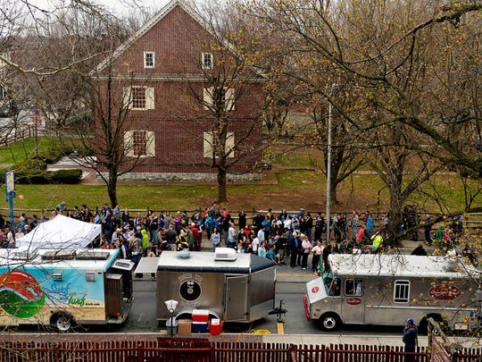 The York County Heritage Trust's Colonial Courthouse is visible as several hundred people wait in lines at food trucks Surf and Turf, Here We Dough and Bountiful Feast Roving Restaurant during the second Foodstruck event on Friday, April 11, 2014. The second Foodstruck event featured 27 food trucks and about a dozen non-food vendors on North Pershing Avenue between West Philadelphia and West Market Streets on Friday, April 11, 2014. Chris Dunn -- Daily Record/Sunday News