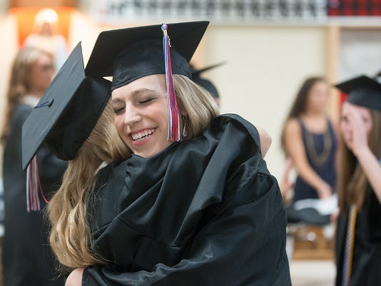 Seniors Madison Stockton and Katie Overdorff embrace each other before commencement at Delone Catholic High School on May 29,