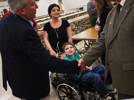 Jackson Salemme, 7, with his mother, Cara, background, looks up with his pair of sunglasses in hand as Sen. Mike Folmer shakes hands with Rep. Will Tallman at a May 1 forum on medical cannabis.