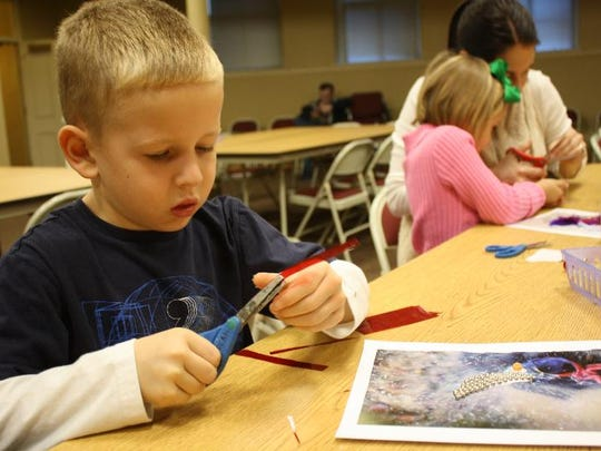 Brandon Lone, 6, cuts a piece of cellophane to enhance his photo of a flightless bird, while his sister, Calli, 4, and mother, Stephanie Lane, work on another photo during the Photos for Fingers Free Family Fun Workshop at the Carnegie Center for Art & History on Saturday.
