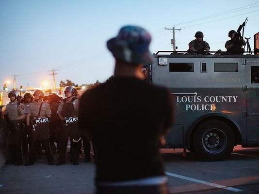 Police stand watch on Wednesday as demonstrators protest the shooting death of teenager Michael Brown in Ferguson, Mo., a St.