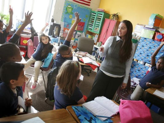 Fourth-graders raise their hands during Elizabeth Recla's science class at Multicultural Academy in Pittsfield Township last fall.