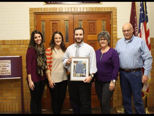 The St. Elizabeth High School yearbook staff dedicated the 2016 yearbook to Christopher Matarese (center), the school's director of technology. Joining him for the Feb. 1 presentation were, from left, his sister Angela Matarese Palmer '05; his wife Amanda Hanny Matarese, a former St. Elizabeth French teacher; and his parents Janet Fontana Matarese '76 and Daniel Matarese '76.