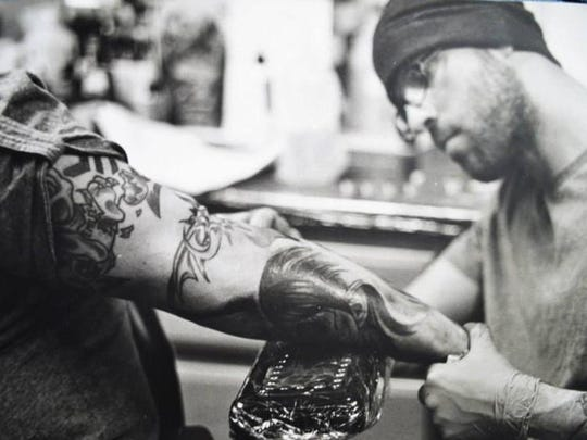 Doug Anderson tattooing a client.