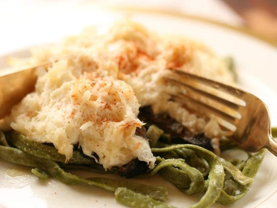 Crab-stuffed portabella is served on garlic buttered spinach fettuccine.