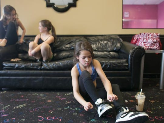 Skylar Slaughter, age 10, ties her laces before dance practice at Dance Designs in Prospect. Slaughter is pursuing a career in the performing arts. Jan., 30, 2013