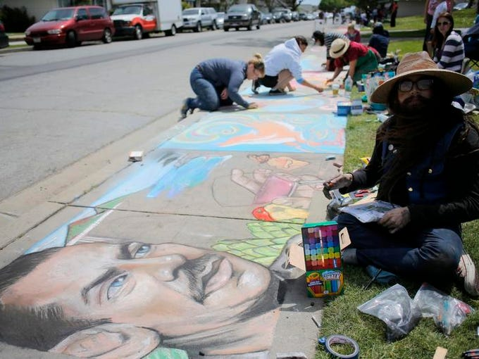 Victor Vasquez de la Rocha works on his sidewalk portrait of John Steinbeck on Saturday during the Chalk in the Park benefit in Spreckels.