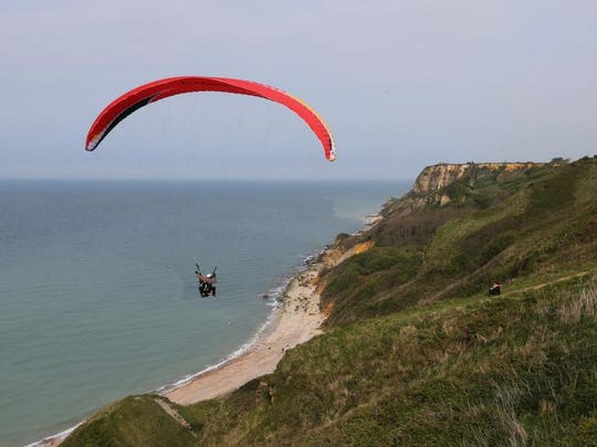 People paragliding over the D-Day beaches, in Port en Bessin, western France. Local officials estimate that several hundred thousand tourists will flock to Normandy this summer, attracted by the 70th anniversary of D-Day.