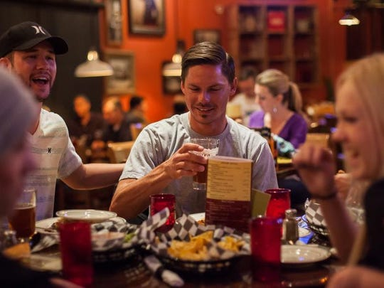 "Chad Seegmiller and David Barnard dine with friends at George's Corner Restaurant in downtown St. George in this 2014 file photo. The restaurant is one of many that prepare alcohol in a back room in keeping with Utah's ""Zion Curtain"" law to prevent family-friendly businesses from making alcohol drinks within view of young diners, although a bill awaiting the governor's signature may ease the restrictions on the industry."