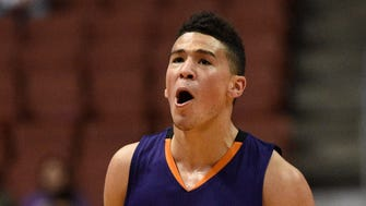 Phoenix Suns guard Devin Booker reacts after making a shot during the first half of an NBA preseason basketball game against the Los Angeles Lakers in Anaheim, Calif., Friday, Oct. 21, 2016.