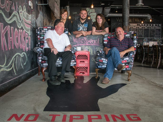 Partners Bob Conway, far left, and Mark Schultz, far right, sit in the entry of Newport restaurant Packhouse Meats with servers Kimber Schultz, Suz Schultz and Matthew Johnson. The restaurant opened in January 2014 with a no tipping policy. Servers are untraditionally paid by set salaries above minimum wage and commission.
