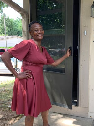 Florence Baseke opens the door to her first apartment. A special adaptive doorbell was installed for Baseke, who is deaf.
