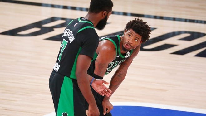 Celtics Jaylen Brown, left, and Marcus Smart talk during the fourth quarter of Thursday night's Game 2 against the Heat.