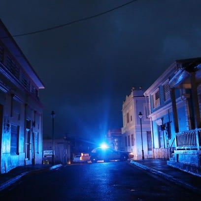 A police car patrols on a darkened street three weeks