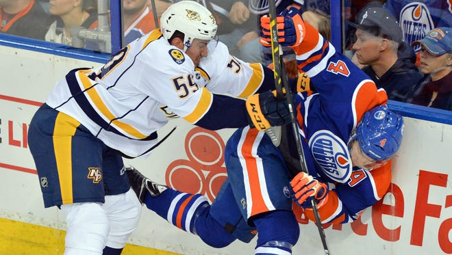 Nashville Predators defenseman Roman Josi (59) checks Edmonton Oilers left wing Taylor Hall (4) into the boards at Rexall Place.
