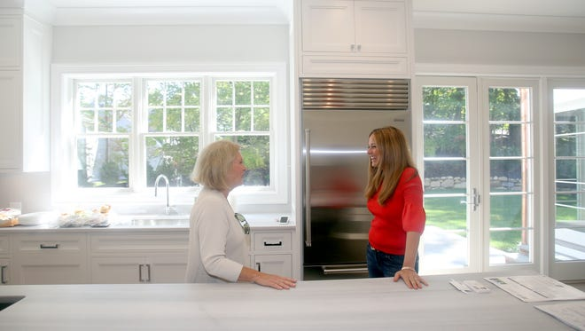 Heather Harrison of Platinum Drive Realty, right, speaks with Pat Ciulla, a mortgage banker with Wells Fargo, at a home that she is selling in Scarsdale Sept. 13, 2017. Harrison spoke about homebuyers who are willing to pay cash for homes, as opposed to taking out mortgages.