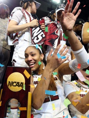 South Carolina forward A'ja Wilson (22) and guard Tiffany Davis (15) celebrate on the podium after defeating the Mississippi State in the 2017 women's national championship game.