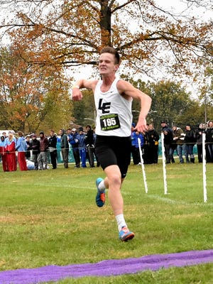 Dustin Horter of Lakota East punches the air in excitement as he set a new course record fininshing 1st in the boys Division 1 run at the 2017 OHSAA Troy Regional Cross Country Championships, Oct. 28, 2017.