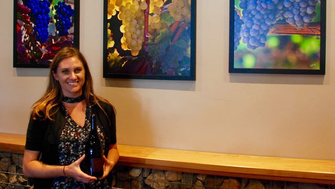 Kristen McIntyre, manager of the tasting room at McIntyre Wines, holds a bottle of Pino Noir next to photos of grapes taken in the company's vineyard in the Santa Lucia Highlands. The tasting room is in the Cross Roads Shopping Center in Carmel Valley.