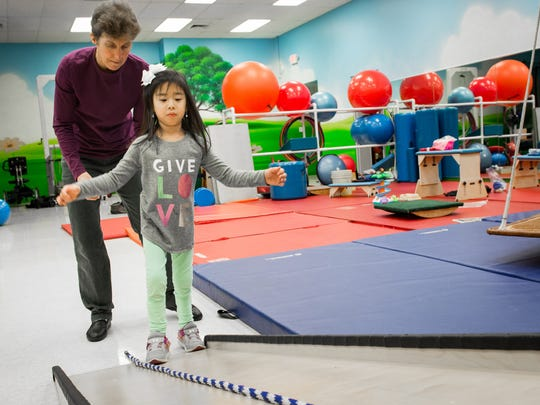 Miah Dillingham walks during  a session with Easterseals Rehabilitation Center Therapist Patty Balbach.