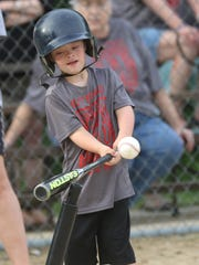 Carson Dick, 7, hits the ball during a match up of