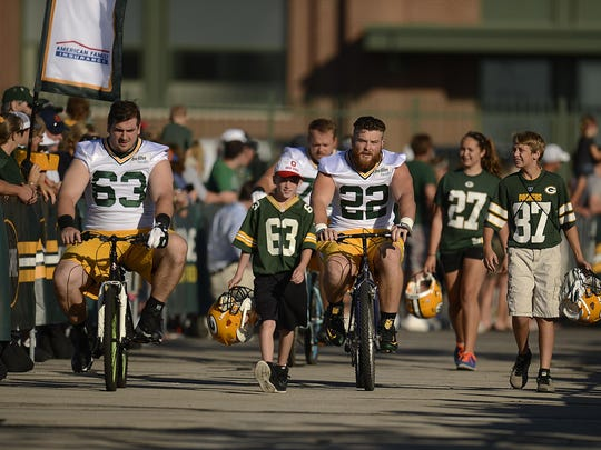 Green Bay Packers center Corey Linsley (63) and fullback Aaron Ripkowski (22) ride bikes to Packers training camp practice at Ray Nitschke Field on Thursday.