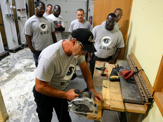 Instructor Barry Bartynski shows how to make a straight, 90-degree cut without a line using a circular saw during a class of the BOP Program Aug. 30, 2016 in Lansing.