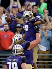Washington's Dante Pettis is lifted up by teammate Trey Adams after Pettis scored a touchdown on a pass reception against Fresno State in the first half of an NCAA college football game, Saturday, Sept. 16, 2017, in Seattle. (AP Photo/Elaine Thompson)