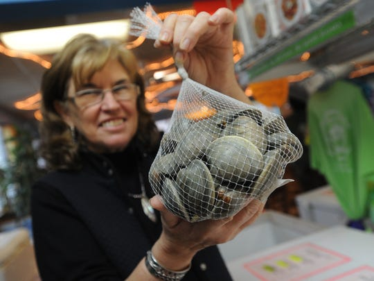 Jean Mariner holds a bag of aquacultured littleneck clams at the Great Machipongo Clam Shack in Nassawadox, Va. on Wednesday, Nov. 26, 2014. A customer recently discovered a large purple clam pearl in a clam that was purchased there. The clams were grown locally by Billy Bowen.