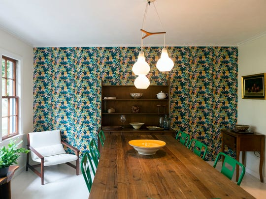 "Allison Alexander created a feature wall in the dining room with this brightly colored wallpaper. ""I wanted something warm, something distinctive,"" she says. ""We sit down to dinner in here every night."""