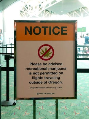 Signs in the PDX terminal remind passengers that state and federal laws prohibit taking marijuana across state lines.