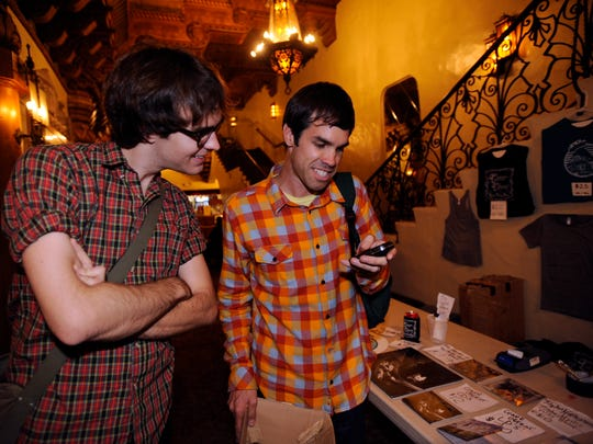 Aaron Gomes of Sound N Vision, right, shows Michael Davis of Los Angeles a text from his wife at the Fox Theatre before the Conor Oberst concert in 2008. Through the nonprofit Sound N Vision, Gomes helps orchestrate concerts and has become a major force in the Visalia music scene.