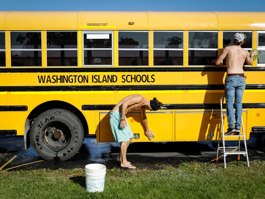 """Bartenders Stanley Usinowicz, Boulder, Colo. and Luke Downing, Leeds, United Kingdom were part of a team that washed and waxed the """"new"""" used school bus the Washington Island School District received in 2017, Sept. 19, 2017."""