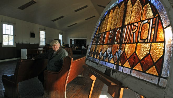 Pastor John Mitchell of Mt Pleasant Church in Millville sits on a church pew near the stained glass, which was one of the items salvaged from fire.  April 5, 2016