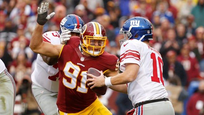 New York Giants quarterback Eli Manning (10) is sacked by Washington Redskins outside linebacker Ryan Kerrigan (91) in the second quarter Nov. 29 at FedEx Field.
