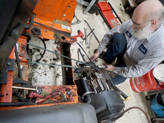 Don Elliott repairs a lawnmower engine Monday afternoon