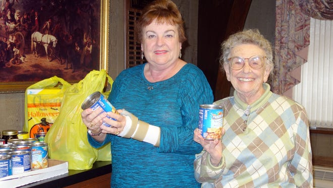 Norene Ritter (left) and Josephine Pagano, members of the Woman's Club of Vineland, are pictured with a portion of the food donations club members collected for donation to the food bank at the First United Methodist Church in Vineland.