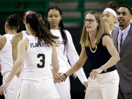 Michigan's Katelynn Flaherty (3) and the rest of the players are greeted at the bench by head coach Kim Barnes Arico, right, during a timeout in the second half of a first-round game against Northern Colorado at the NCAA women's college basketball tournament in Waco, Texas, Friday, March 16, 2018. (AP Photo/Tony Gutierrez)