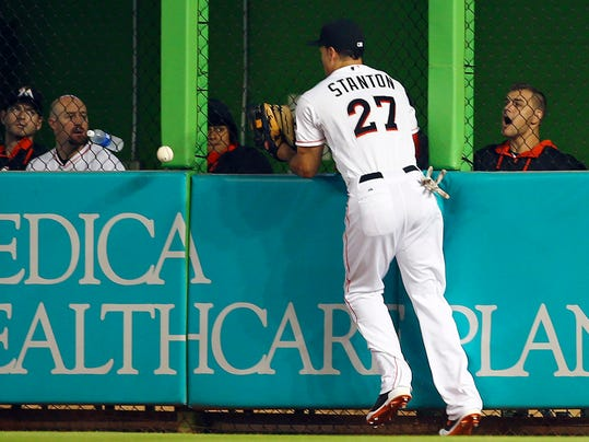 Miami Marlins' Giancario Stanton misplays a ball hit by Chicago Cubs' Chris Coghlan during the second inning of a baseball game in Miami, Wednesday, June 18, 2014.  (AP Photo/J Pat Carter)