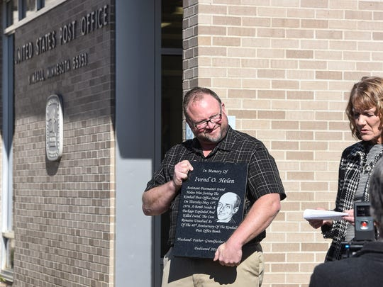Author Robert Dudley holds a plaque in memory of Ivend Holen as Kimball mayor Tammy Konz speaks Tuesday, Oct. 18, during a dedication ceremony in Kimball.