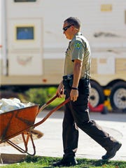 An MCSO deputy uses a wheelbarrow to move dead dogs (none in this picture) at Green Acre Dog Boarding in Gilbert.