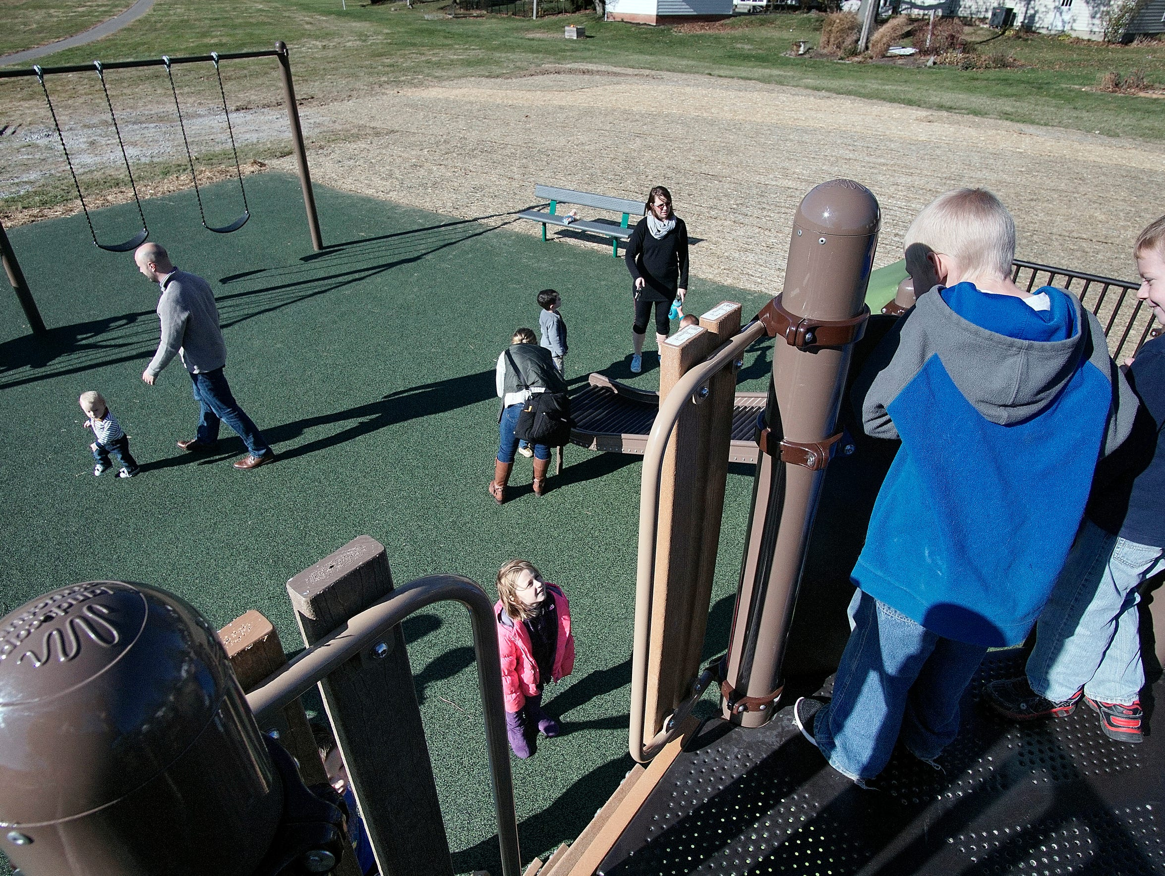 Kids play Sunday morning in a new playground designed