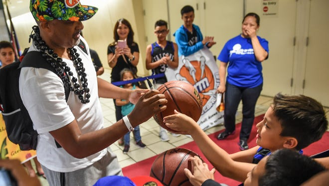 """Phil Handy, assistant coach for the Cleveland Cavaliers, takes time to autograph a basketball for Phillip Guerrero shortly after arriving at the A.B. Won Pat International Airport on Wednesday, July 29. Handy will be accompanied by two NBA players for the 2015 """"94 Feet of Game"""" basketball clinics and exhibition game, which will sharpen the skills of selected Guam youth basketball players."""