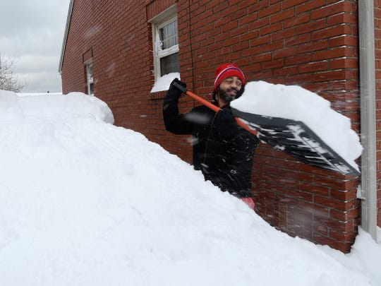 Patrick Harden clears snow from the roof of his car on Dec. 26, 2017, in Erie, Pa.