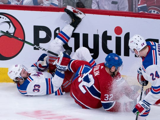 New York Rangers' Phillip Di Giuseppe, left, and Montreal Canadiens' Christian Folin slide into the boards during the first period of an NHL hockey game Thursday, Feb. 27, 2020, in Montreal. (Paul Chiasson/The Canadian Press via AP)