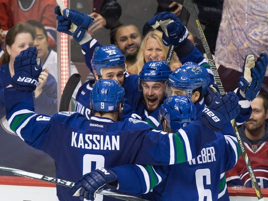 Vancouver Canucks' Shawn Matthias, centre, celebrates his goal against the Montreal Canadiens with teammates Zack Kassian, from left to right, Shawn Matthias, Luca Sbisa, of Switzerland, and Yannick Weber, of Switzerland, during the third period of an NHL hockey game, Thursday, Oct. 30, 2014 in Vancouver, British Columbia. (AP Photo/The Canadian Press,  Darryl Dyck)